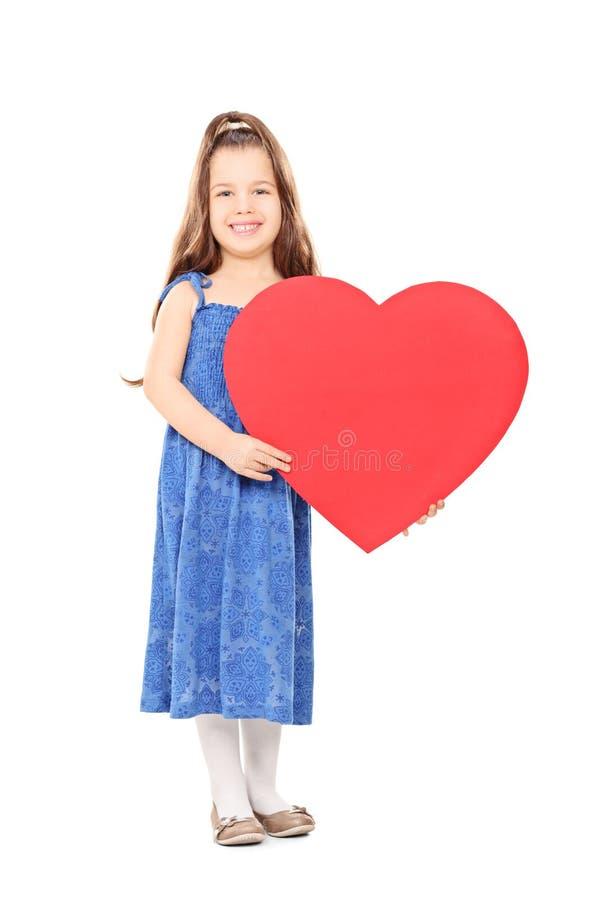 Petite fille tenant un grand coeur rouge image libre de droits