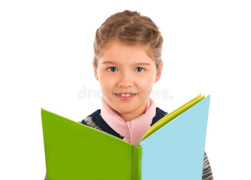 Petite fille tenant un livre d'histoire verte et bleue image libre de droits
