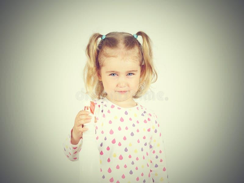 Petite fille tenant une bouteille de jet d'eau image libre de droits