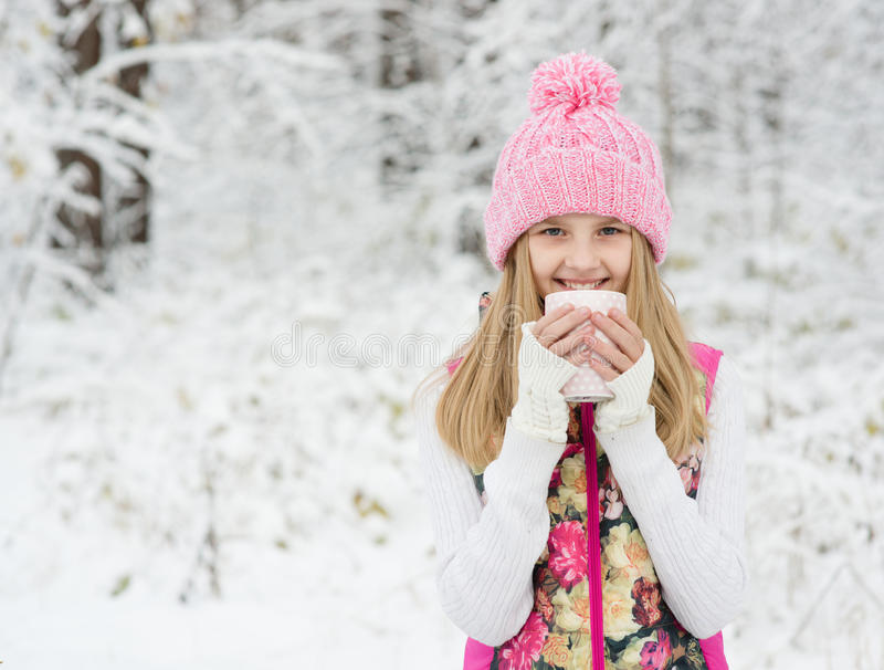 Petite fille tenant une tasse de boisson et de sourire chauds photos libres de droits