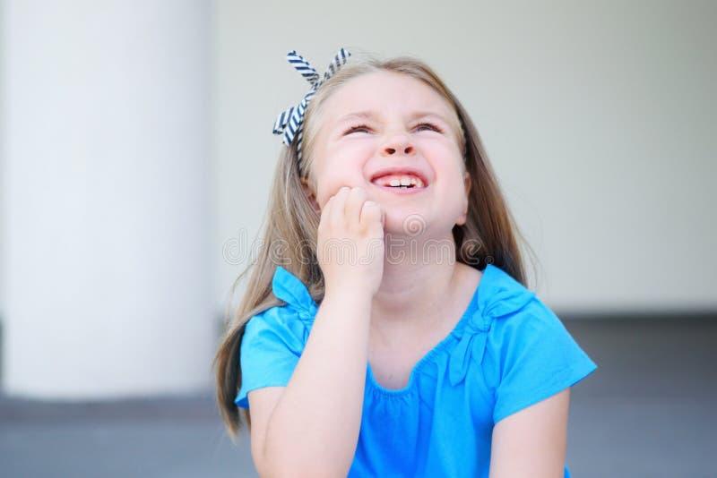 Petite fille triste avec de longs cheveux blonds souffrant du mal de dents photo libre de droits