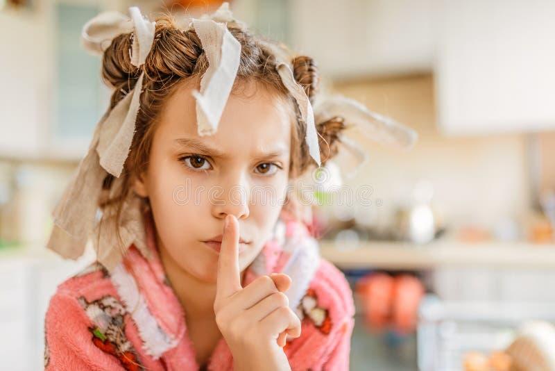 Petite fille triste avec des bigoudis de cheveux sur sa tête photos stock