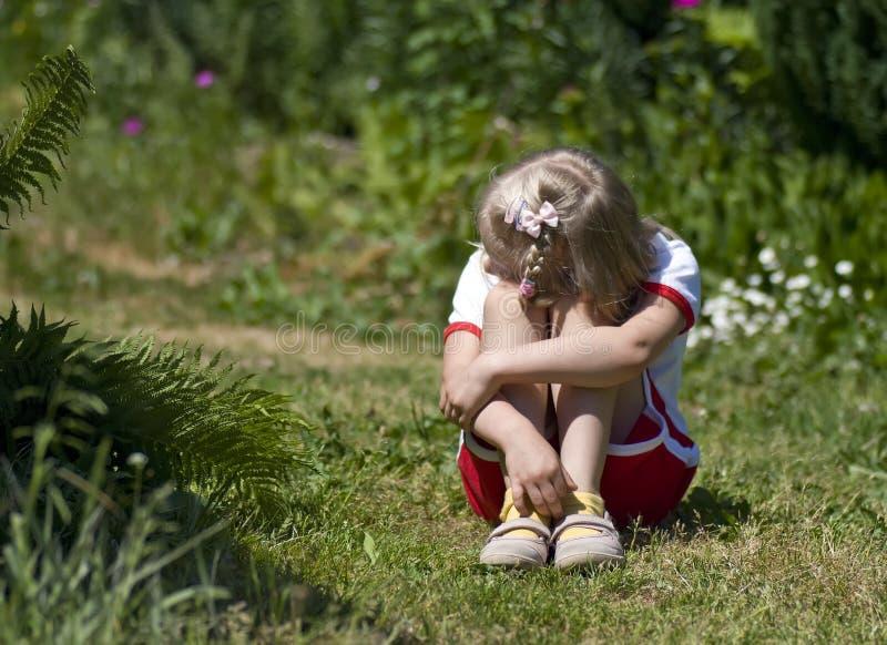 Petite fille triste dans le jardin photos libres de droits
