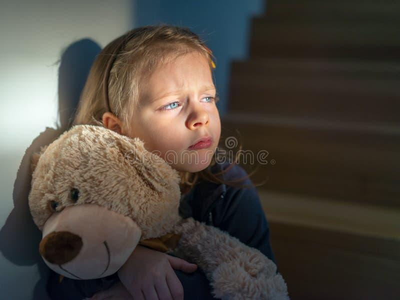 Petite fille triste embrassant son ours de nounours - se sent seul images stock