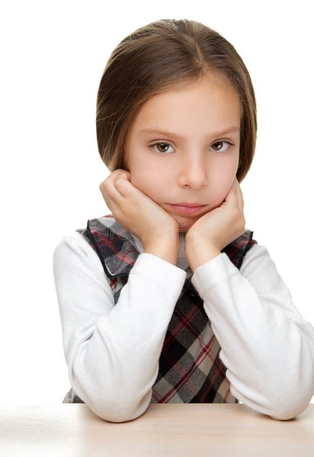 Petite fille triste s'asseyant à la table image libre de droits
