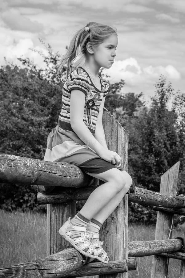 Petite fille triste s'asseyant sur la barrière en bois photographie stock
