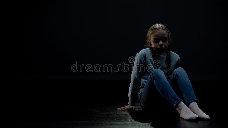 Petite fille triste seul s'asseyant dans la chambre noire, la solitude et le concept de intimidation image stock