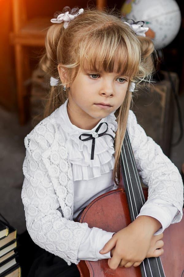 Petite fille triste tenant un violoncelle images libres de droits