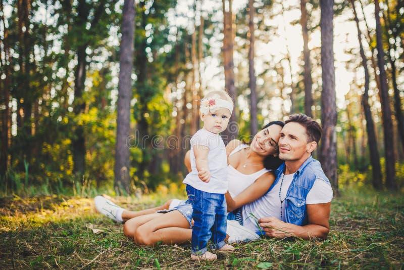 Petite fille un an sur le fond des parents se reposant se trouvant sur l'herbe apprenant à marcher sur la nature en parc Les prem photographie stock