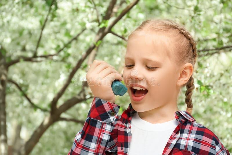 Petite fille utilisant l'inhalateur près de l'arbre de floraison Concept d'allergie photo libre de droits