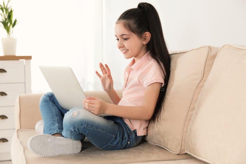 Petite fille utilisant la causerie visuelle sur l'ordinateur portable images stock