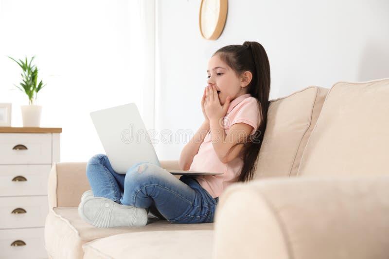 Petite fille utilisant la causerie visuelle sur l'ordinateur portable photos stock