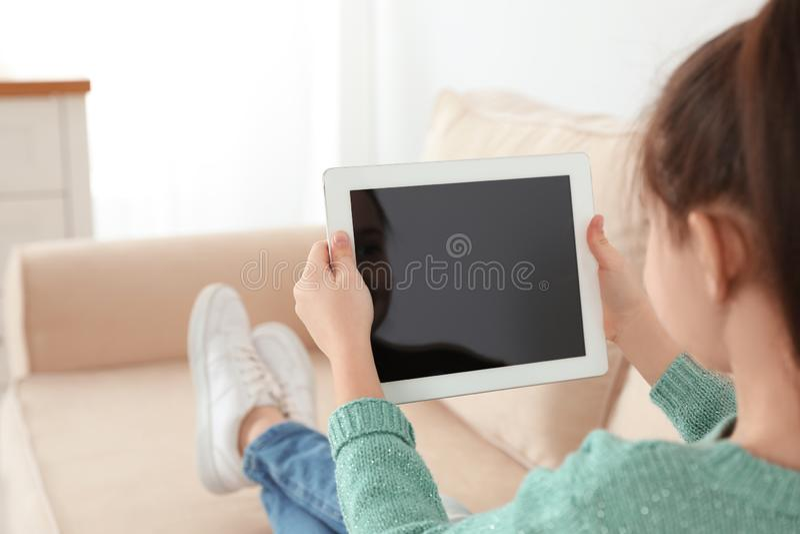 Petite fille utilisant la causerie visuelle sur le comprimé à la maison photo stock