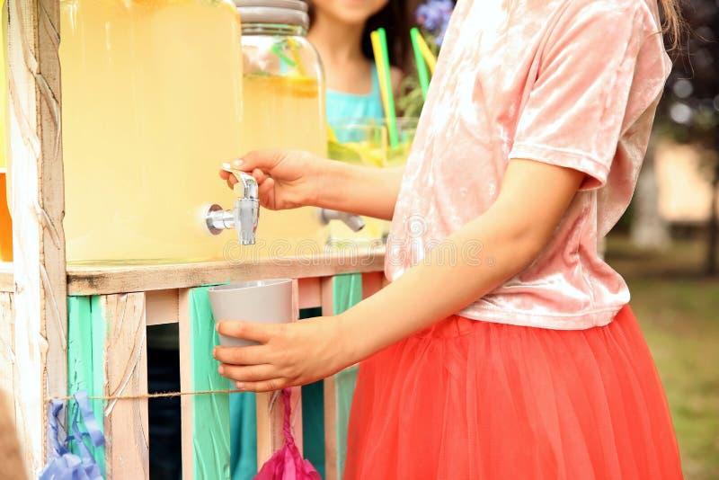 Petite fille versant la limonade naturelle dans la tasse photographie stock