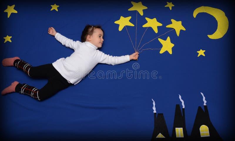 Petite fille volant aux étoiles images libres de droits