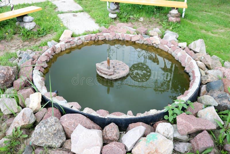 Petite fontaine en pierre faite maison d'étang faite de pavés ronds photo libre de droits