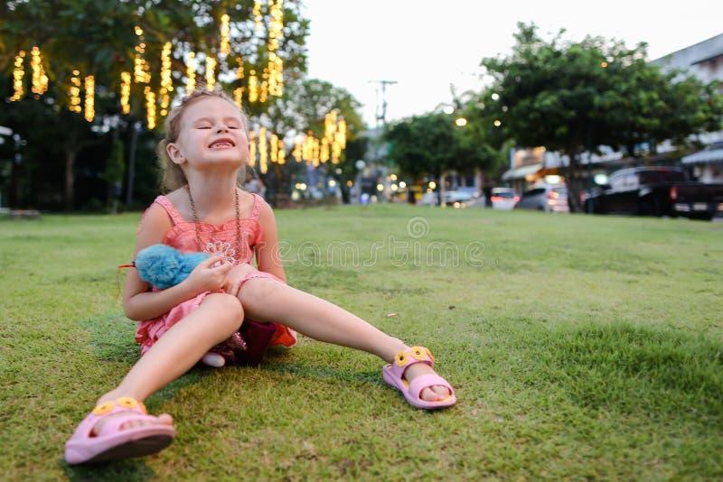 Petite gentille fille s'asseyant sur la pelouse d'herbe, construisant sur le fond photographie stock