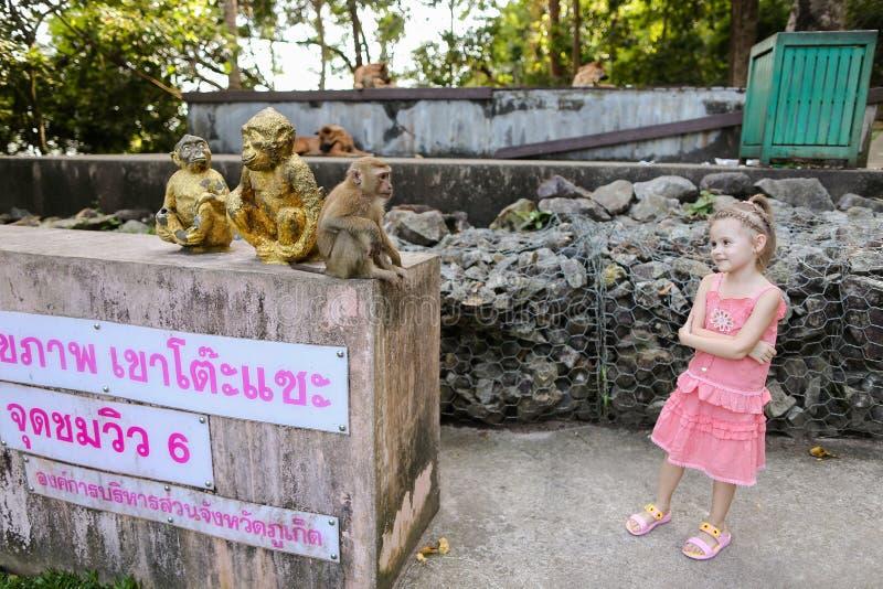 Petite gentille fille tenant les statuettes d'or et le macaco de singe proche au zoo en Thaïlande images libres de droits
