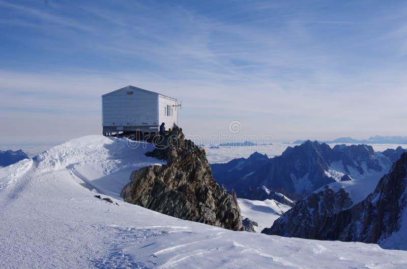 Petite hutte en bois construite sur le dessus d'une colline neigeuse avec stupéfier les montagnes rocheuses à l'arrière-plan photographie stock libre de droits
