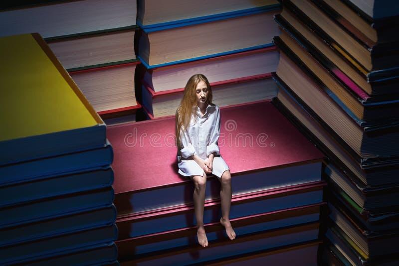 Petite jeune femme s'asseyant sur des livres photographie stock libre de droits