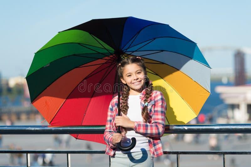 Petite jolie fille se tenant avec le parapluie coloré Fille sur le pont Dissimulation du soleil avec le parapluie Nuances lumineu photos stock