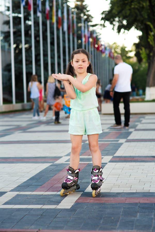 Petite jolie fille sur des patins de rouleau à un parc images stock