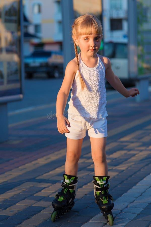 Petite jolie fille sur des patins de rouleau à un parc photographie stock libre de droits
