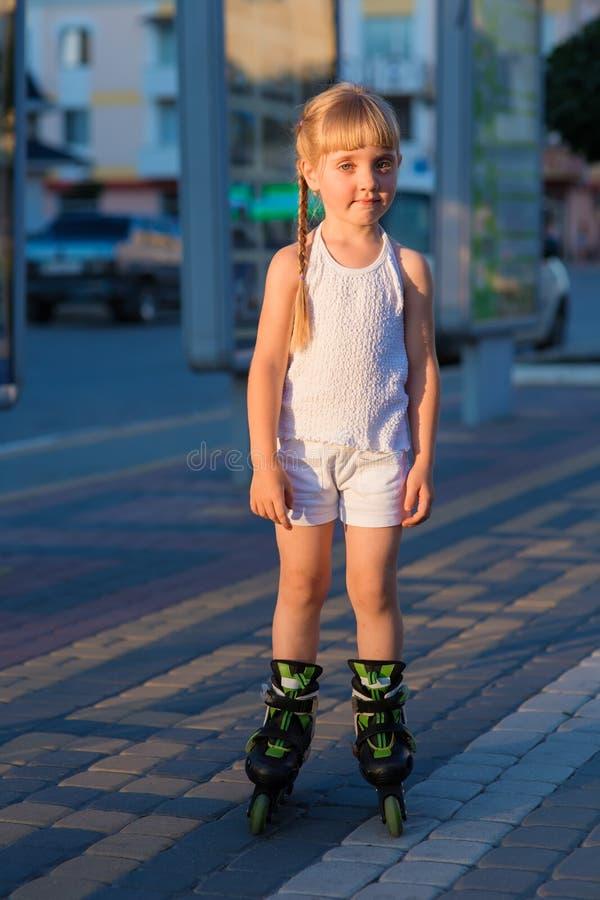 Petite jolie fille sur des patins de rouleau à un parc photo stock