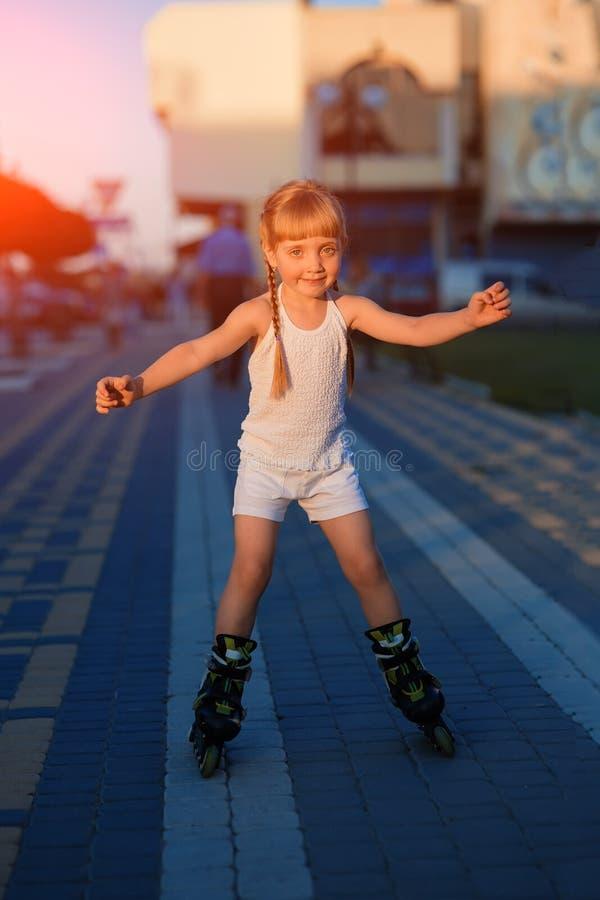 Petite jolie fille sur des patins de rouleau à un parc image stock