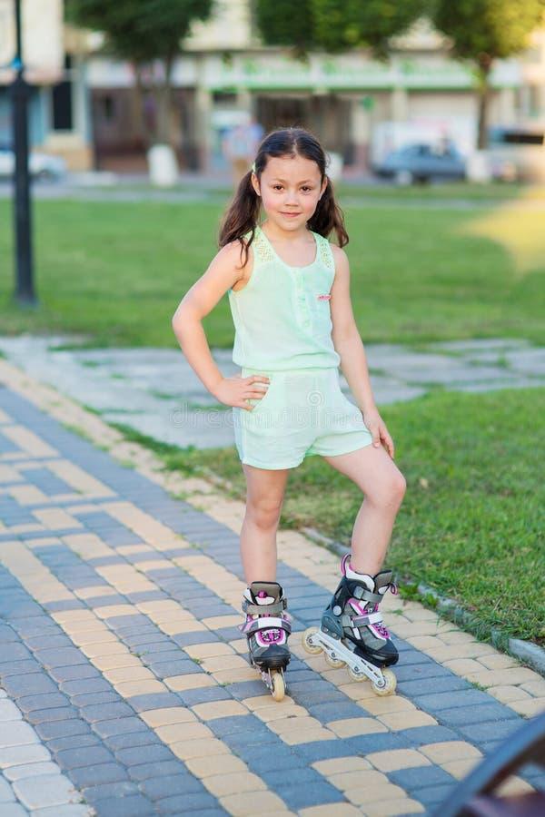 Petite jolie fille sur des patins de rouleau à un parc photographie stock
