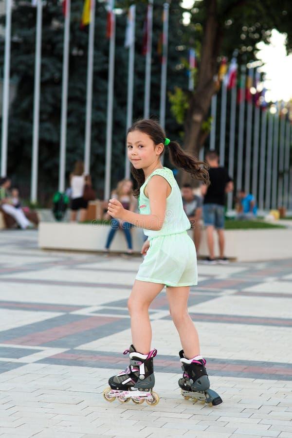 Petite jolie fille sur des patins de rouleau à un parc photos stock