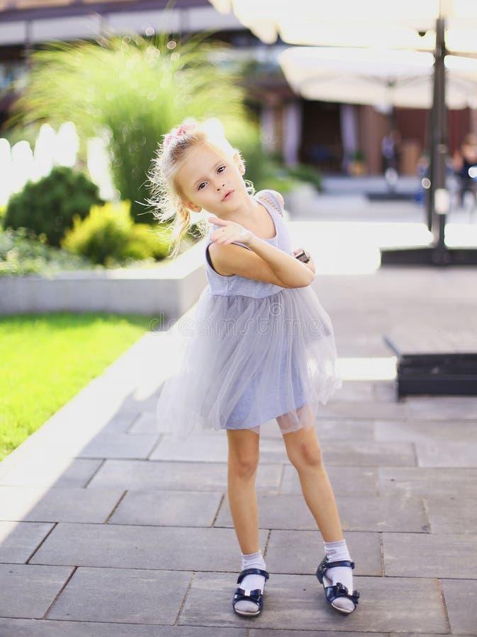 Petite jolie position européenne de fille dans la cour et la robe grise de port photos stock
