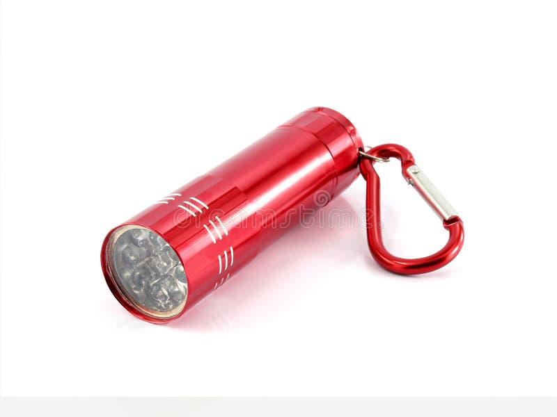 Petite lampe-torche rouge en gros plan en métal avec la lumière de LED et carabiner d'isolement sur le fond blanc photo libre de droits