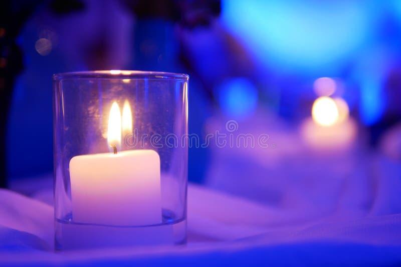 Petite lueur d'une bougie qui ont les taches jaunes sur la lumière pourpre et le fond blanc dans la chambre de la partie de la cé photo libre de droits