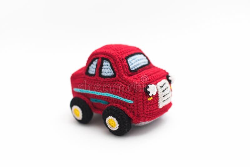 Petite machine rouge tricotée de bébé sur le fond blanc image libre de droits