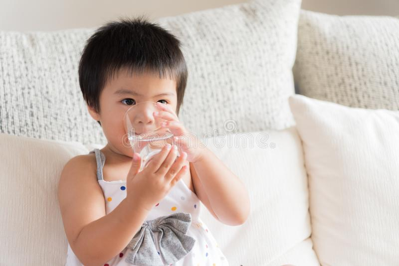 Petite main asiatique heureuse de fille tenant le verre et la La d'eau potable  images stock