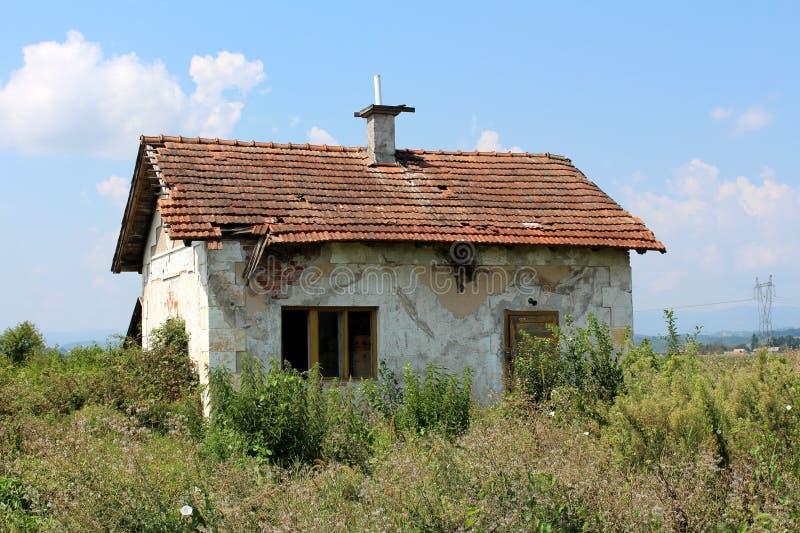 Petite maison abandonnée de briques rouges avec la façade blanche délabrée et les tuiles de toit détruites complètement entourées image libre de droits