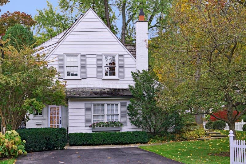 Petite maison blanche avec le pignon et la clôture photographie stock libre de droits