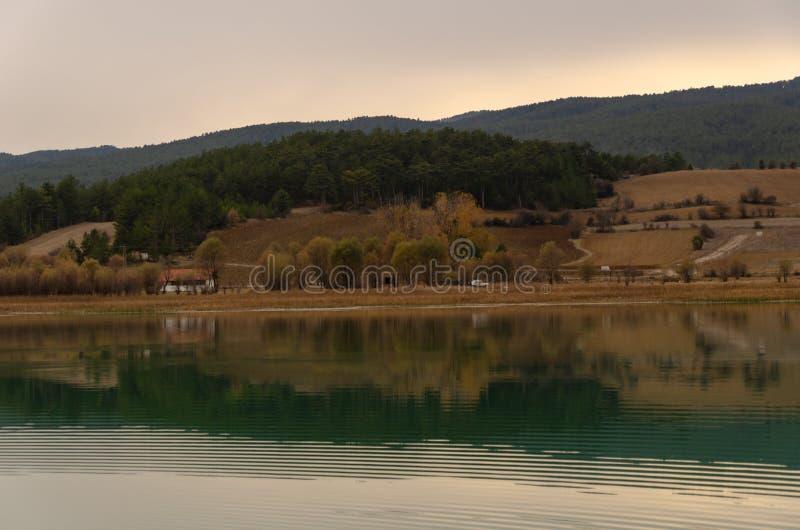 Petite maison blanche avec une belle réflexion sur le lac devant lui photo stock
