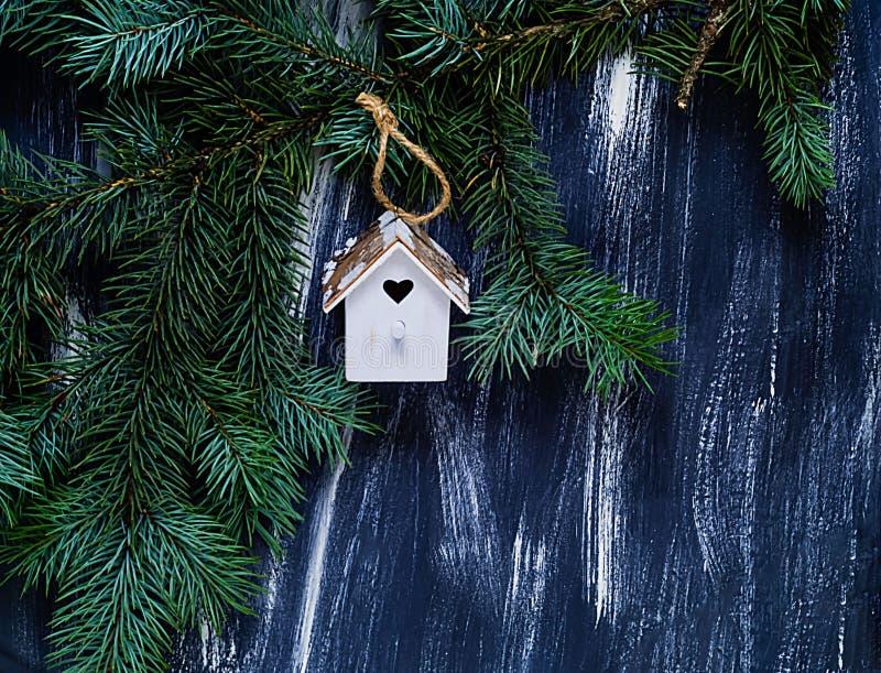Petite maison blanche d'élément décoratif avec un coeur sur un fond en bois bleu d'arbre de sapin de branche, l'espace libre pour images stock