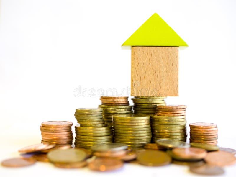 Petite maison de blocs se tenant sur une pile des pièces de monnaie images stock