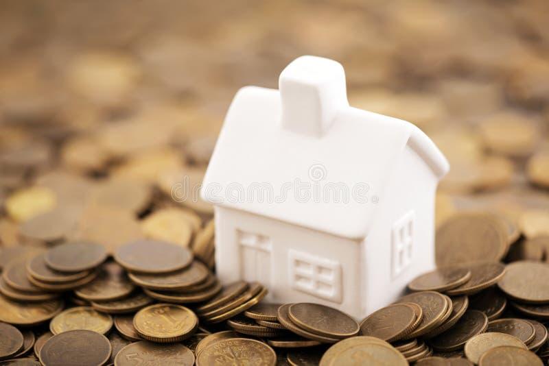 Petite maison de jouet sur des pièces de monnaie image libre de droits