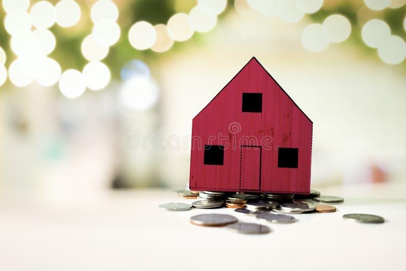 Petite maison rouge se tenant sur un tas des pièces de monnaie photo stock