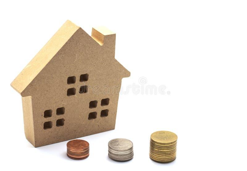 petite maison se tenant sur des pièces de monnaie Le concept de l'achat du habita image stock