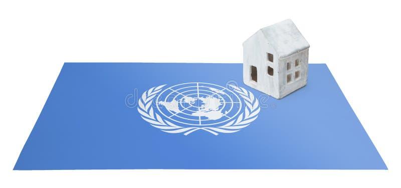 Petite maison sur un drapeau - les Nations Unies images stock