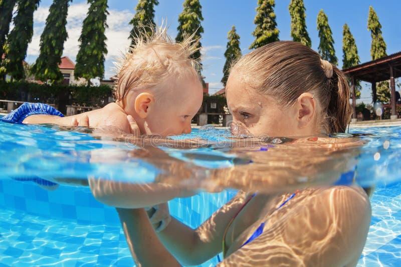Petite natation de bébé garçon dans la piscine extérieure avec la mère photo libre de droits