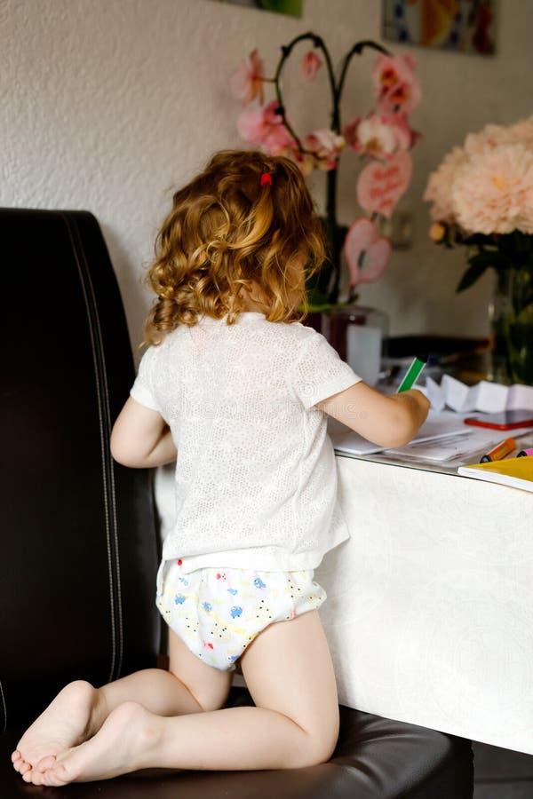 Petite peinture mignonne de fille d'enfant en bas âge de bébé avec les crayons colorés à la maison Enfant heureux en bonne santé  photo stock