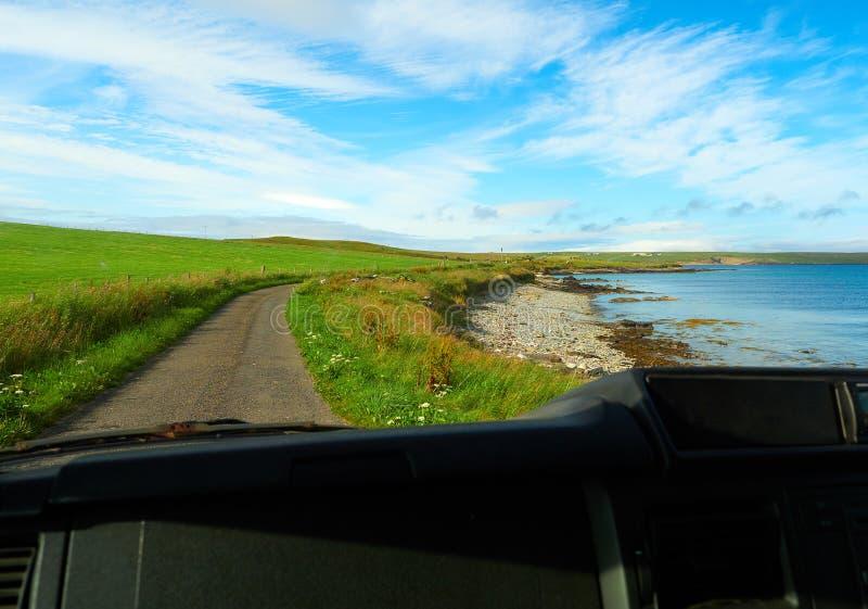 Petite plage de roche et de cailloux vue de l'intérieur d'une voiture, Îles d'Orkney, Ecosse photos stock