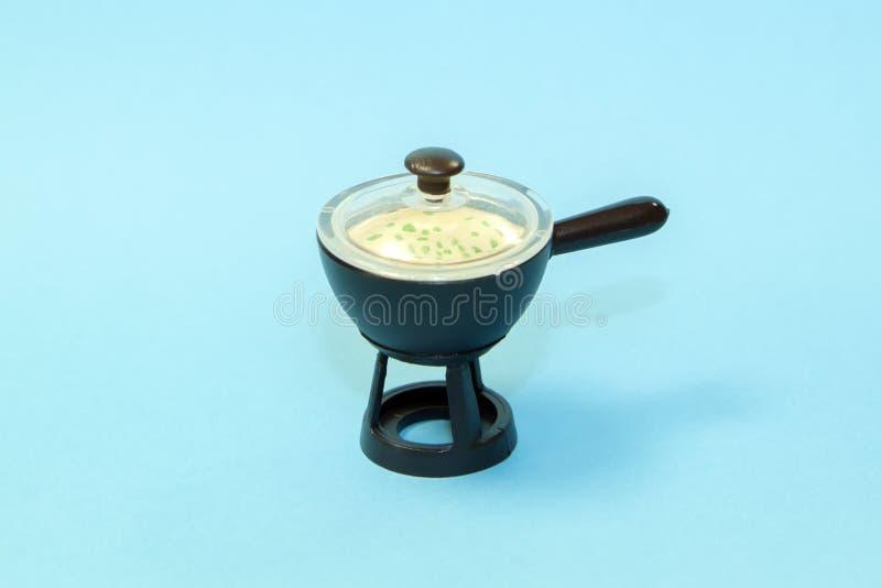 petite poêle à frire de jouet avec couvercle et légumes dans de la crème aigre sur fond bleu image stock