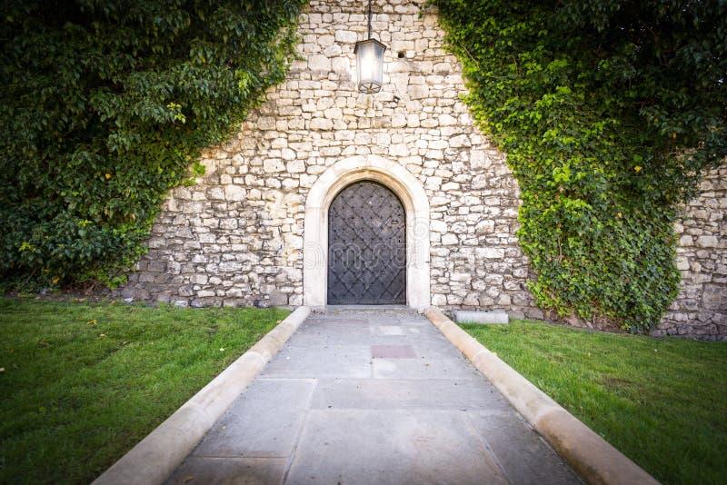 Petite porte au mur en pierre du vieux château photo libre de droits